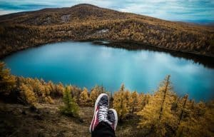 A man sitting on the top of mountain and watching lake.